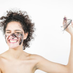 smiling-happy-young-woman-removing-facial-mask-against-white-background_23-2147901150